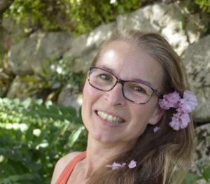 Portrait von Zoë D. Lorek mit Brille und rosa Blüten im Haar, lachend.